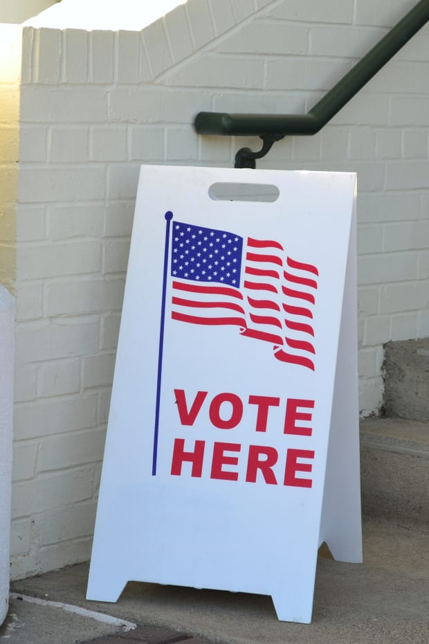 a-sign-showing-folks-where-to-vote-outside-a-voting-poll-location-copy-space-background-negative_t20_pYA948