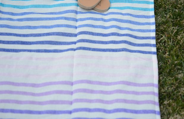{A striped beach blanket we've been using on our lawn on warm afternoons}