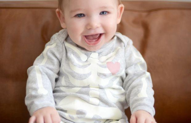 {Sloan showing off one of two teeth, in her skeleton onesie, naturally}