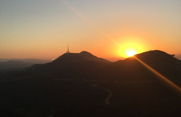 {A bright-orange sunset over the Hollywood Hills}