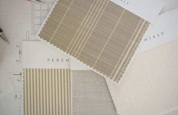 Reviewing neutral fabric swatches for our outdoor sectional