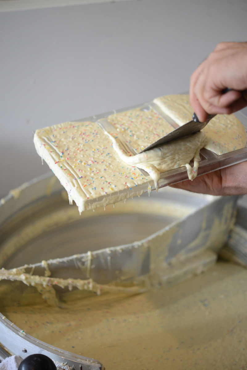 Birthday Cake bar batter being fitted to a chocolate bar mold.