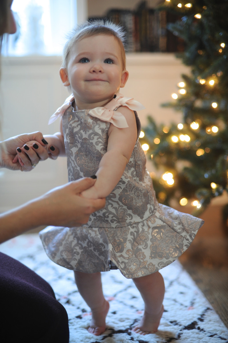 Tip toes by the tree in a metallic jacquard dress by Janie and Jack.