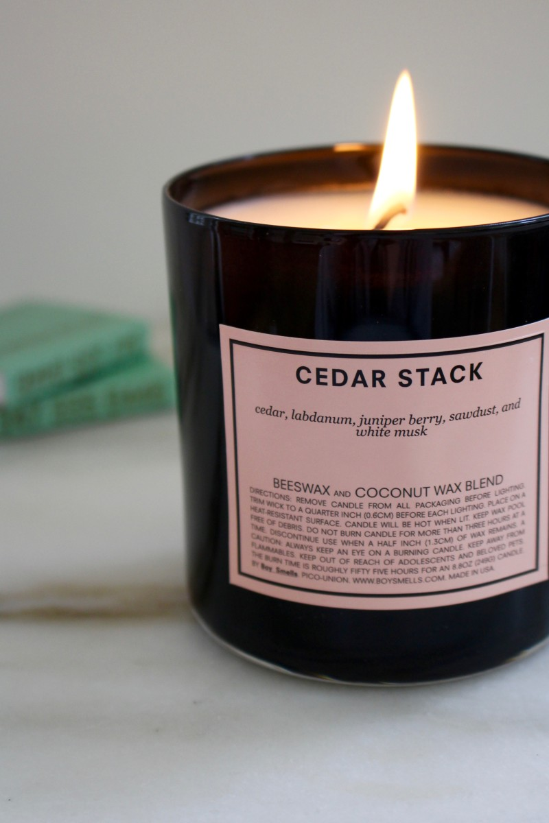 Boy Smells Candle in Cedar Stack