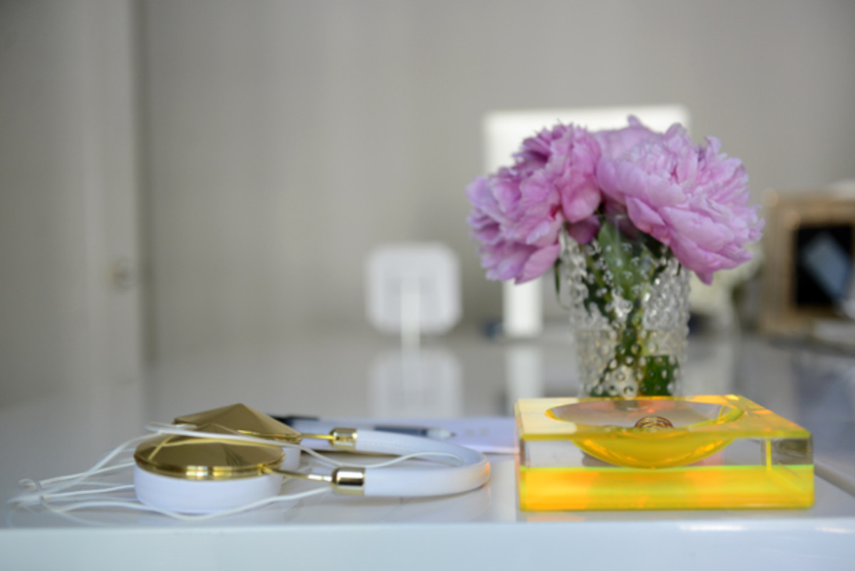 {Desk essentials: headphones, paper clip bowl, and fresh flowers}