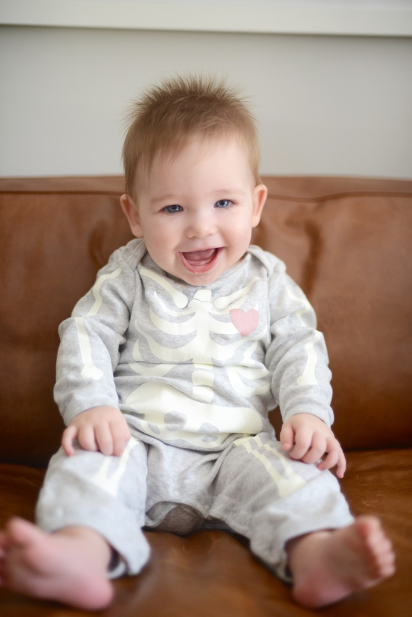 {Sloan showing off one of two teeth, in her skeleton onesie, naturally}