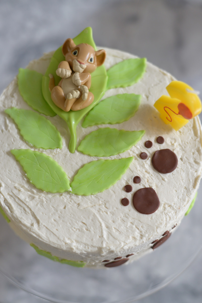 My mom's incredible cake with fondant paw prints, leaves, and a baby Simba topper