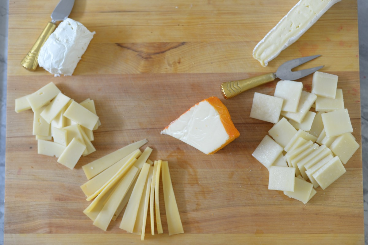 Clockwise from top-left: Goat cheese, brie, Parmesan-young Gouda blend, Pecorino-Romano, Fontina, and Port Salut (center, with the orange rind).