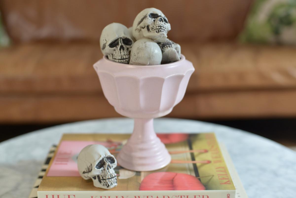 {Miniature skulls fill up a vintage goblet}